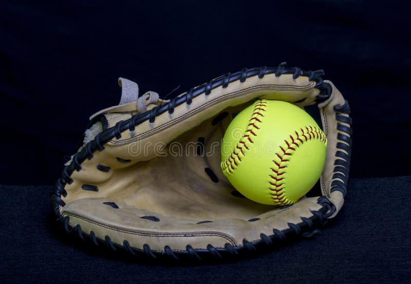 Fastpitch垒球有黄色球的俘获器露指手套 库存照片