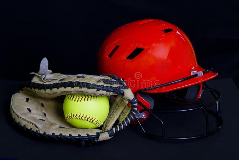 Fastpitch softballboll, handske & hjälm arkivbild