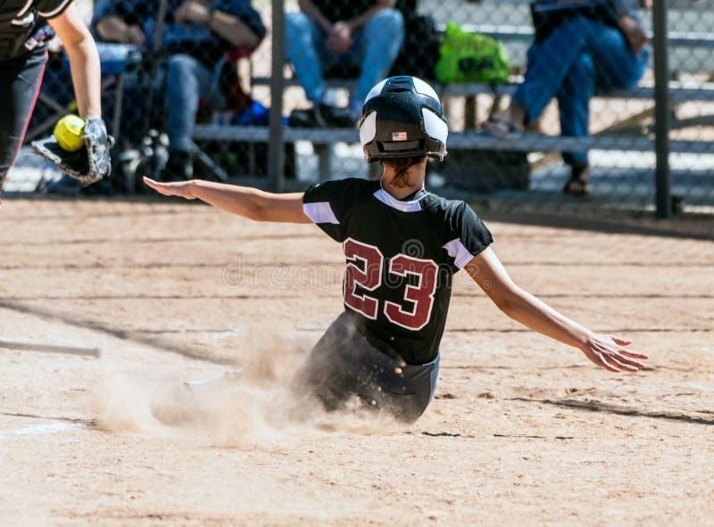 Fastpitch softballspelare som fokuseras på leken royaltyfria bilder