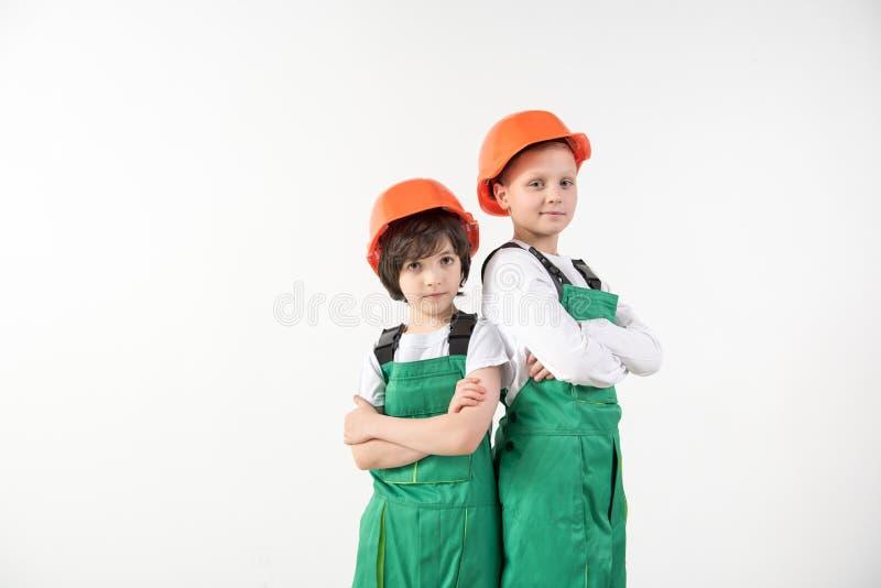 Fastsittande pojkar som står i konstruktörutrustning royaltyfri foto