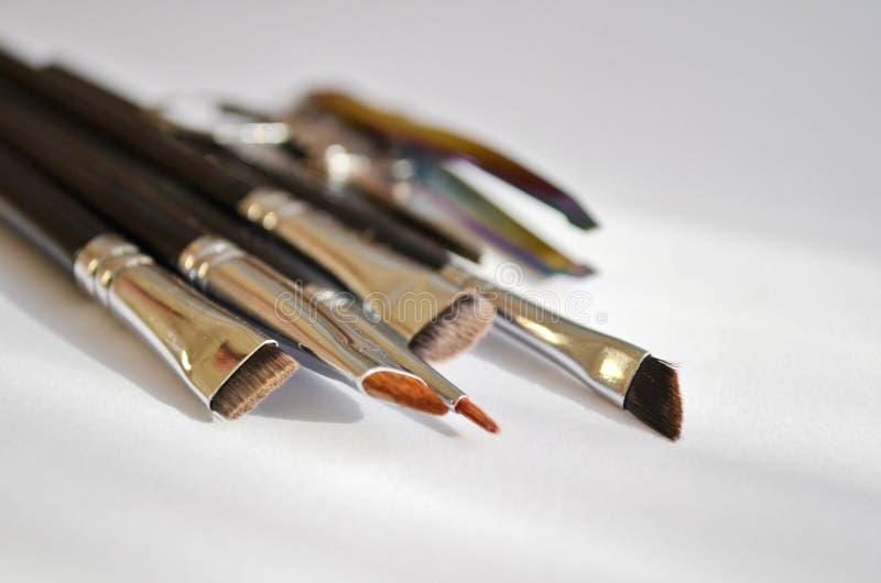 Fastställd hjälpmedelsminkkonstnär en uppsättning av olik borstar för makeupkonstnär och sax och pincett i naturligt ljus arkivbilder