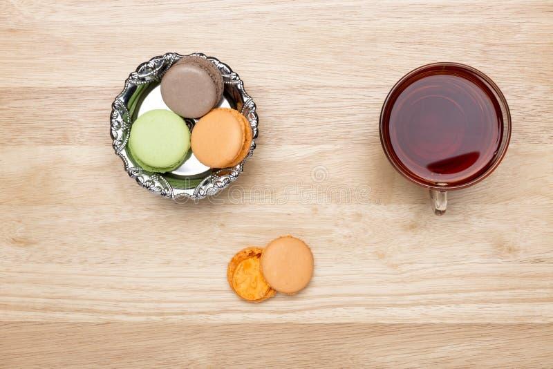 Fastställda färgrika makron och glass kopp av svart te arkivbilder