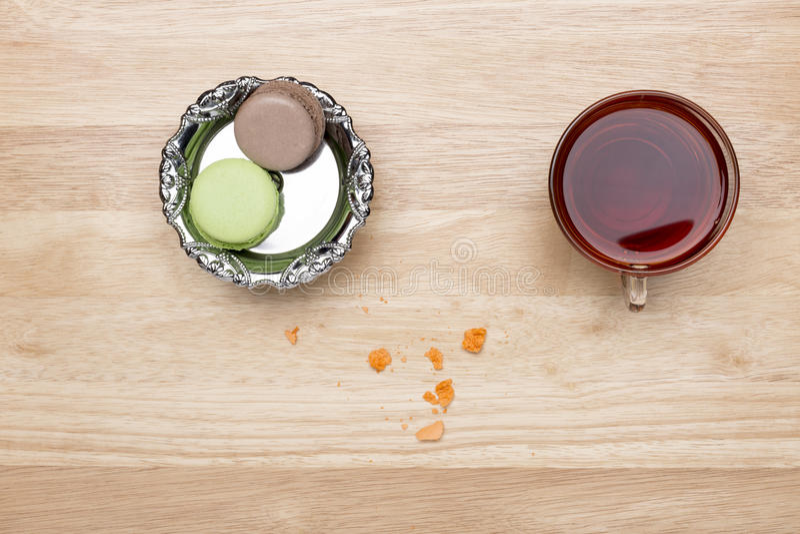 Fastställda färgrika makron och glass kopp av svart te royaltyfria foton