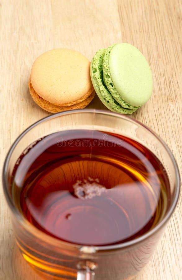 Fastställda färgrika makron och glass kopp av svart te royaltyfria bilder