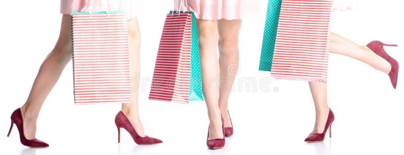 Fastst?llda kvinnaben i r?da skor f?r h?g h?l och kl?nningp?sepacke i handmode royaltyfria foton
