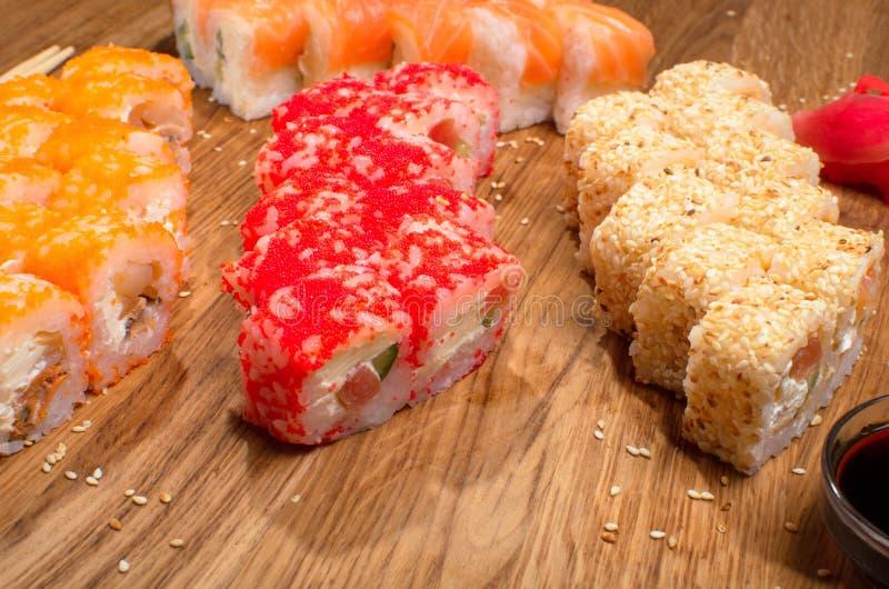 Fastst?llda sushirullar p? en tr?tabell med t?lt soya och ingef?ra smaklig matst?lle Ukrainsk inerpretation f?r Japanis k?k arkivbild