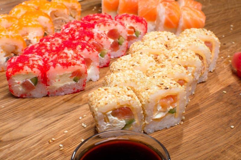 Fastst?llda sushirullar p? en tr?tabell med t?lt soya och ingef?ra smaklig matst?lle Ukrainsk inerpretation f?r Japanis k?k arkivbilder