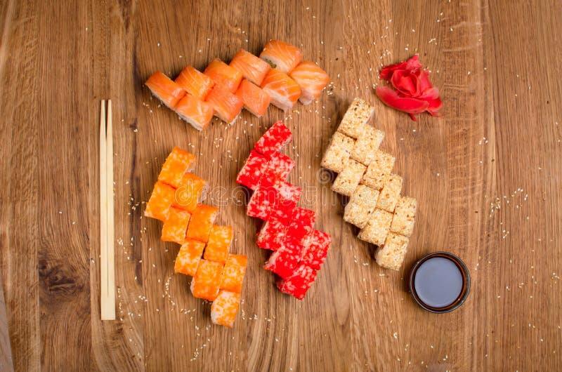 Fastst?llda sushirullar p? en tr?tabell med t?lt soya och ingef?ra smaklig matst?lle Ukrainsk inerpretation f?r Japanis k?k royaltyfri foto