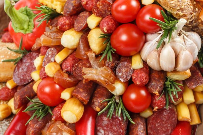 Fastställt bestå av olika variationer av korven, kött, rökt ost, tomater, peppar och bröd som bakgrund arkivbild