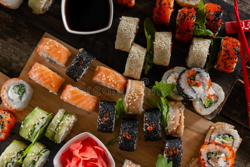 Fastställt matfoto för sushi Rolls tjänade som på brunt trä och kritiserar plattan Övre och bästa sikt för slut av sushi royaltyfri fotografi