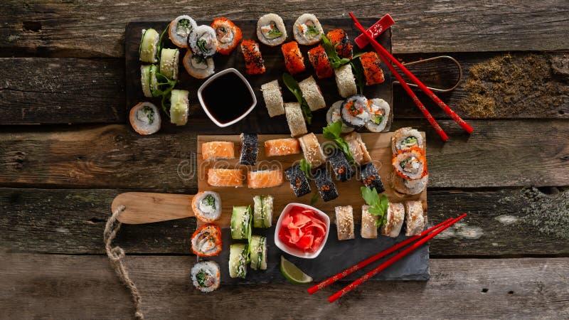 Fastställt matfoto för sushi Rolls tjänade som på brunt trä och kritiserar plattan Övre och bästa sikt för slut av sushi 16 i skö royaltyfri bild