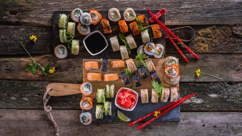 Fastställt matfoto för sushi Rolls tjänade som på brunt trä och kritiserar plattan Övre och bästa sikt för slut av sushi 16 i skö royaltyfri foto