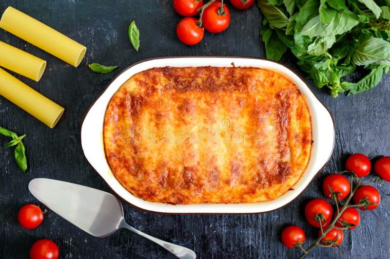 Faszerujący cannelloni z bechamel kumberlandem Cannelloni makaron piec z mięsem, kremowy kumberland, ser na czarnym tle odg?rny w fotografia royalty free