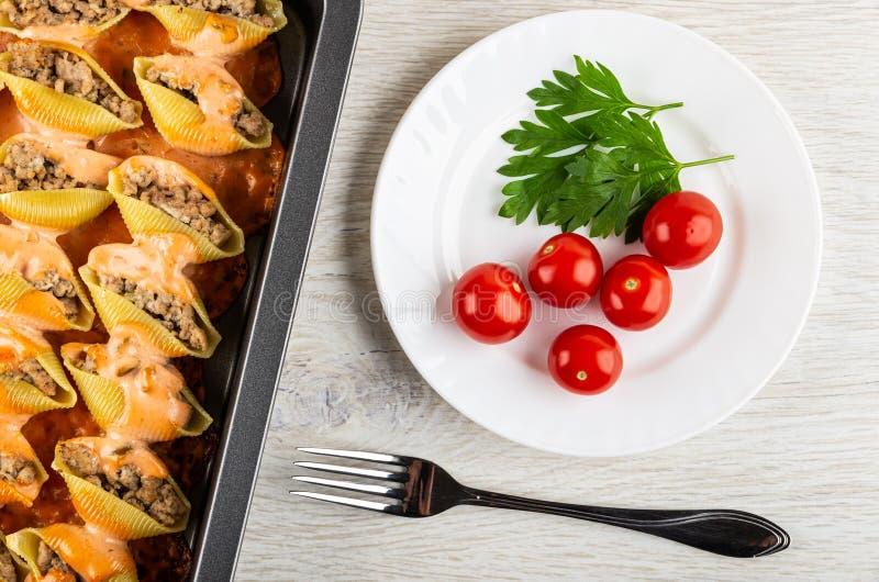 Faszerujący makaronu conchiglie z kumberlandem w kapiącej niecce, talerz z pomidorem, pietruszka, rozwidlenie na drewnianym stole zdjęcia royalty free