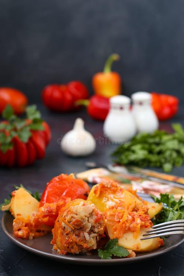 Faszerujący pieprze z mięsem, ryż i pomidorowym kumberlandem, Lokalizować w talerzu na ciemnym tle fotografia stock