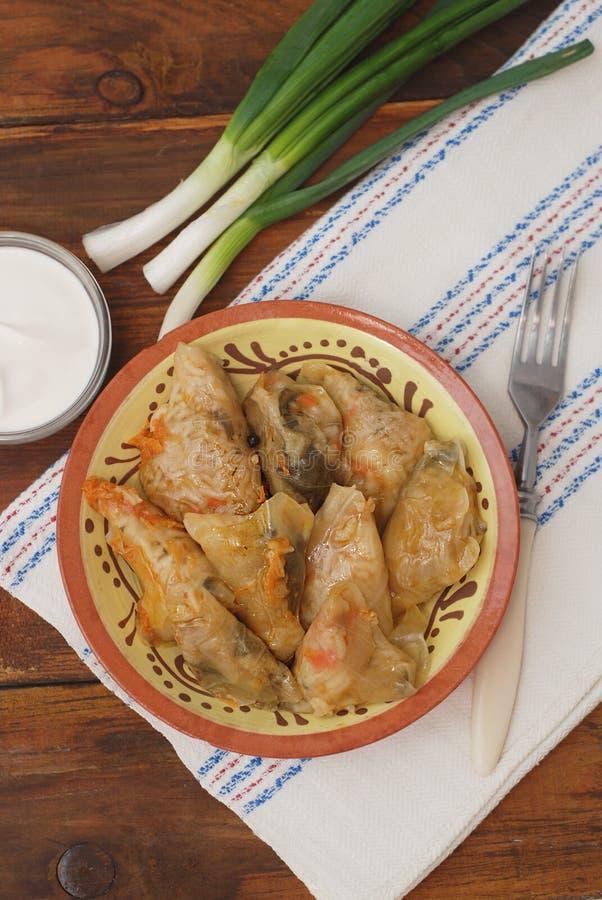 Faszerujący Staczający się Kapuściany mięso w liściach w Ceramicznym talerzu z Białą pieluchą, pietruszka na Nieociosanym Drewnia zdjęcie royalty free