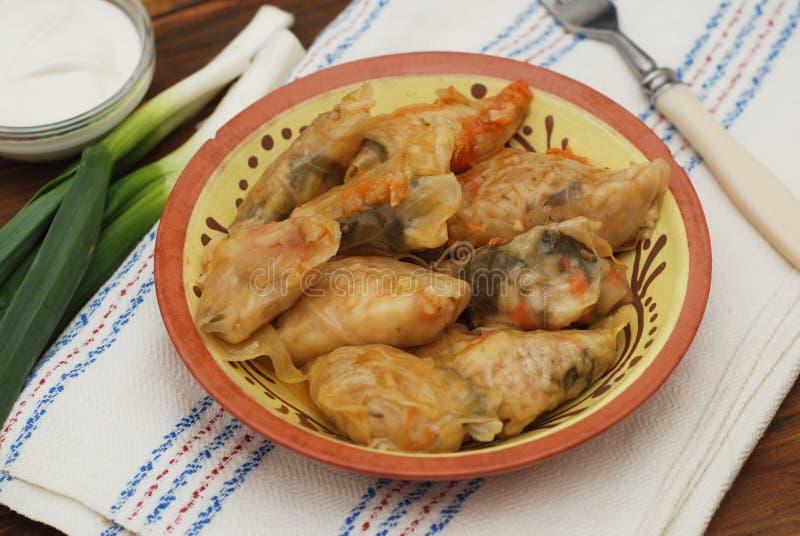 Faszerujący Staczający się Kapuściany mięso w liściach w Ceramicznym talerzu z Białą pieluchą, pietruszka na Nieociosanym Drewnia obraz stock