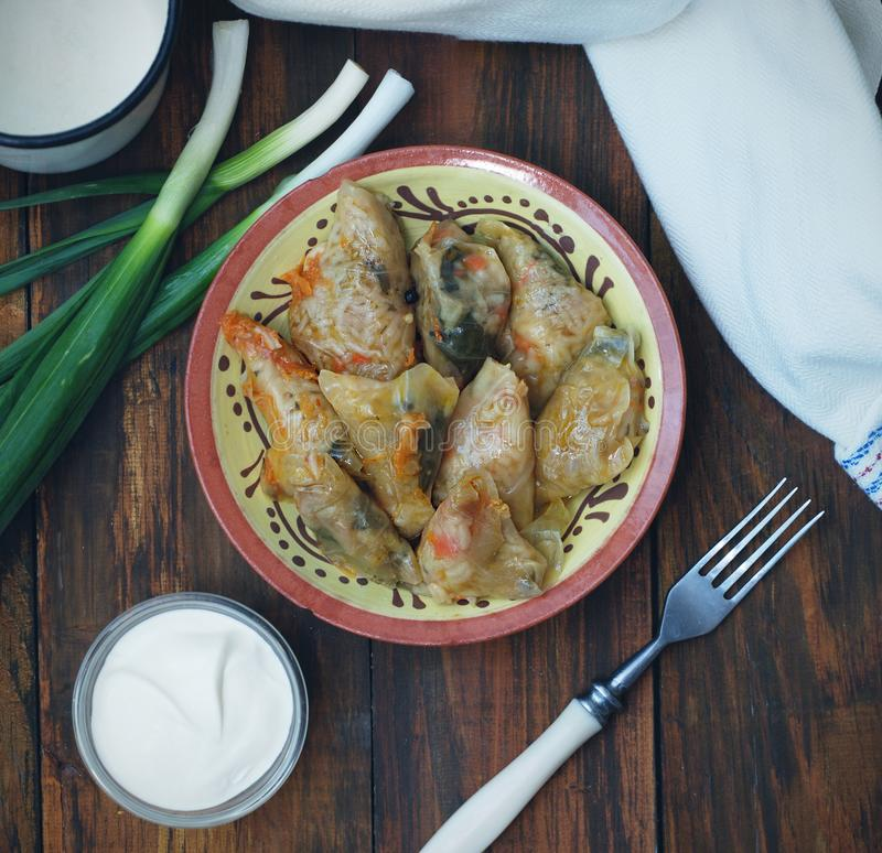 Faszerujący Staczający się Kapuściany mięso w liściach w Ceramicznym talerzu z Białą pieluchą, pietruszka na Nieociosanym Drewnia fotografia royalty free