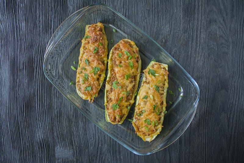 Faszerujący zucchini z minced mięsem i kraciastym serem w szklanym wypiekowym prześcieradle drewniany t?o zmrok obrazy royalty free