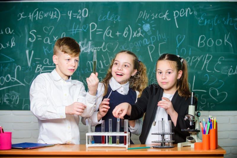 Faszinierende Chemie Gruppenschulschüler studieren Chemie in der Schule Junge und Mädchen genießen chemisches Experiment organisc stockfotos