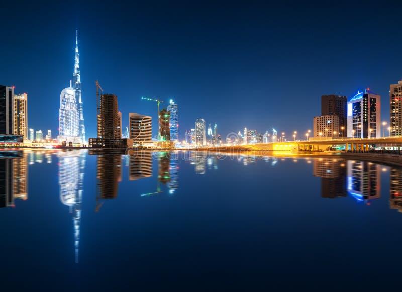 Faszinierende Reflexion von höchsten Wolkenkratzern im Geschäfts-Buchtbezirk während der ruhigen Nacht Dubai, Arabische Emirate stockbild