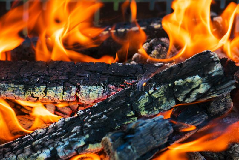 Faszinierendes Feuer, mit glühenden Holz- und sich schlängelnflammen Die Beschaffenheit des brennenden Baums stockbild
