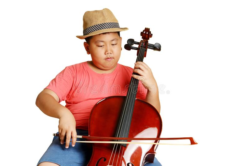 Asian students playing music. A fat Asian boy wearing a hat wearing a pink shirt playing cello music. isolated stock photography