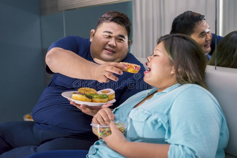 Fat Asian couple eating doughnuts romantically royalty free stock photo