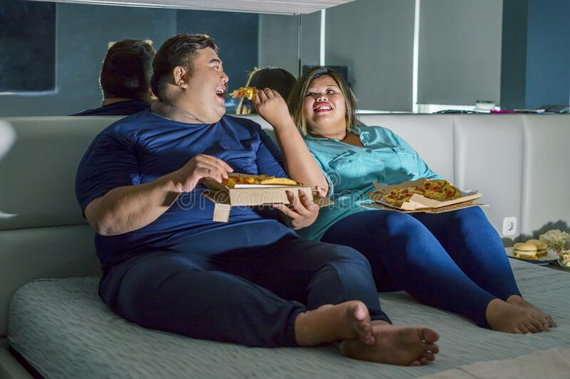 Fat Asian couple eating pizza romantically stock images
