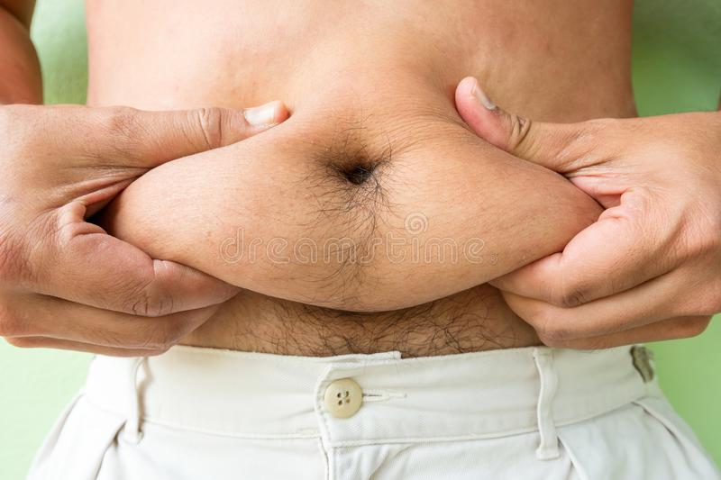 Fat Asian man pinching the excess fat. On his stomach stock image