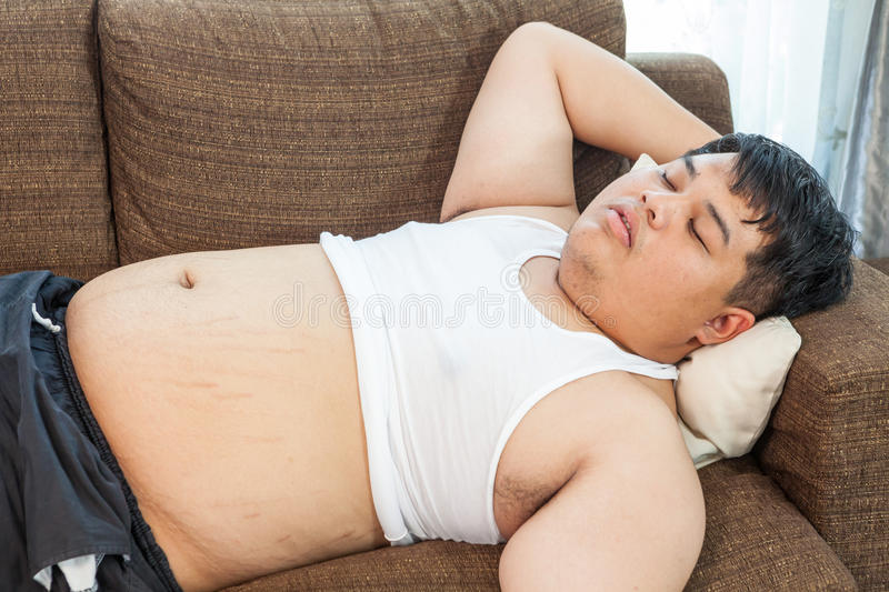 Fat asian man sleeping. On the couch stock images
