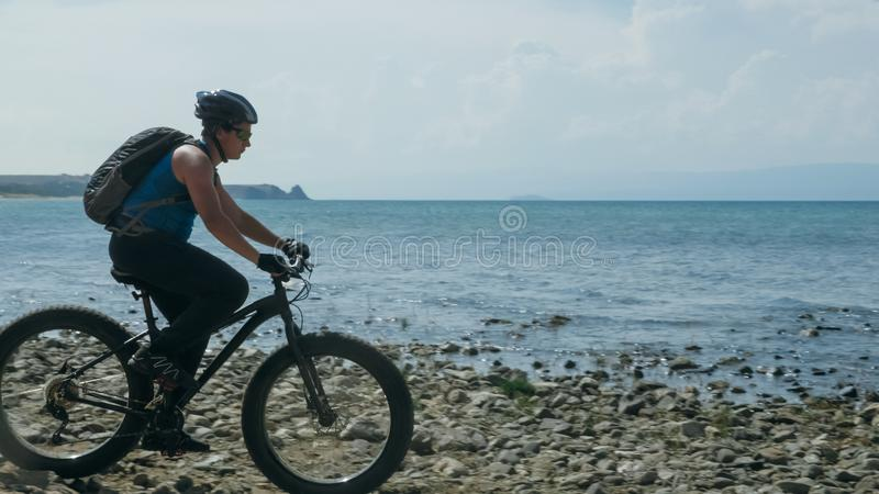 Fat bike also called fatbike or fat-tire bike in summer driving on the beach. The guy is going straight on the beach. On the sand on such a bike ride is not stock images