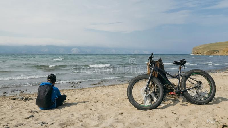 Fat bike also called fatbike or fat-tire bike in summer driving on the beach. The guy sits on the wheel of his bicycle, looks at the sea royalty free stock photo