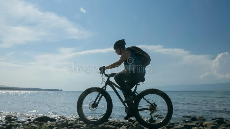 Fat bike also called fatbike or fat-tire bike in summer driving on the beach. The guy is going straight on the beach. On the sand on such a bike ride is not royalty free stock photos