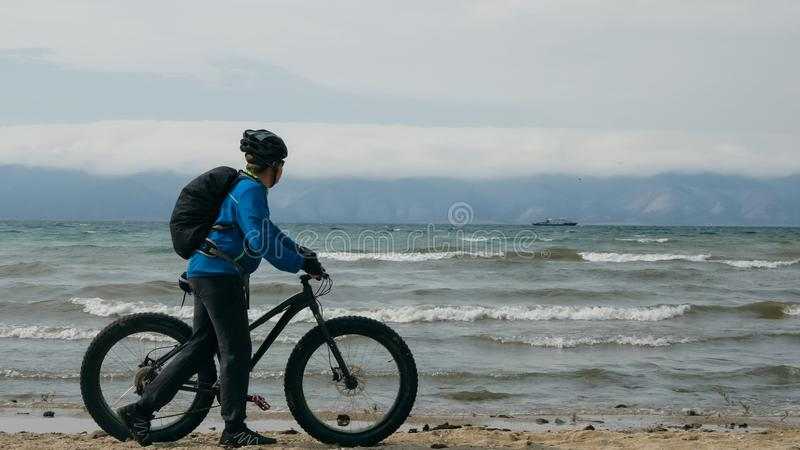 Fat bike also called fatbike or fat-tire bike in summer driving on the beach. The guy is going straight on the beach. On the sand on such a bike ride is not stock image