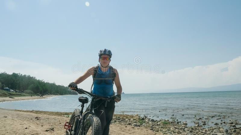 Fat bike also called fatbike or fat-tire bike in summer driving on the beach. The guy is going straight on the beach. On the sand on such a bike ride is not royalty free stock image