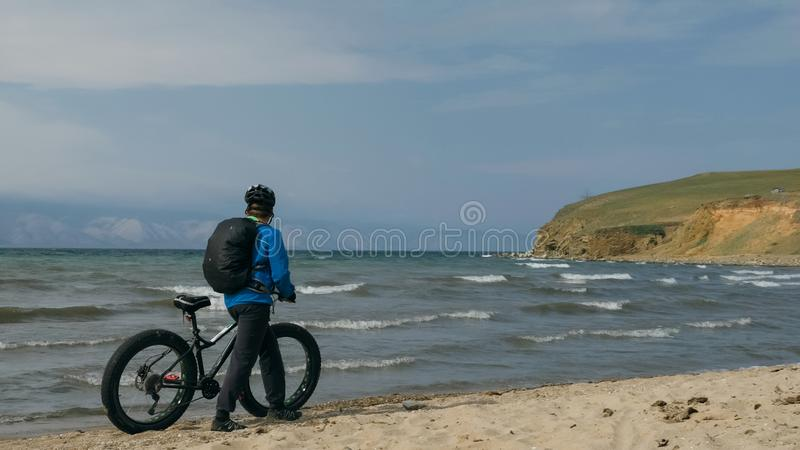 Fat bike also called fatbike or fat-tire bike in summer driving on the beach. The guy is going straight on the beach. On the sand on such a bike ride is not stock photography