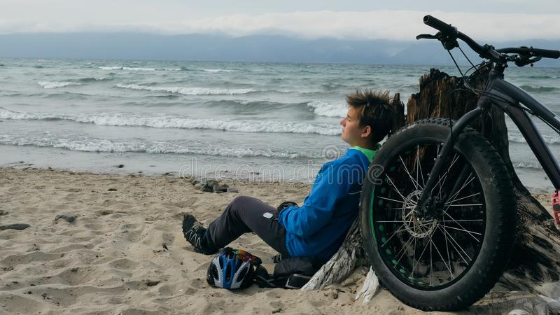 Fat bike also called fatbike or fat-tire bike in summer driving on the beach. The guy sits on the wheel of his bicycle, looks at the sea stock images