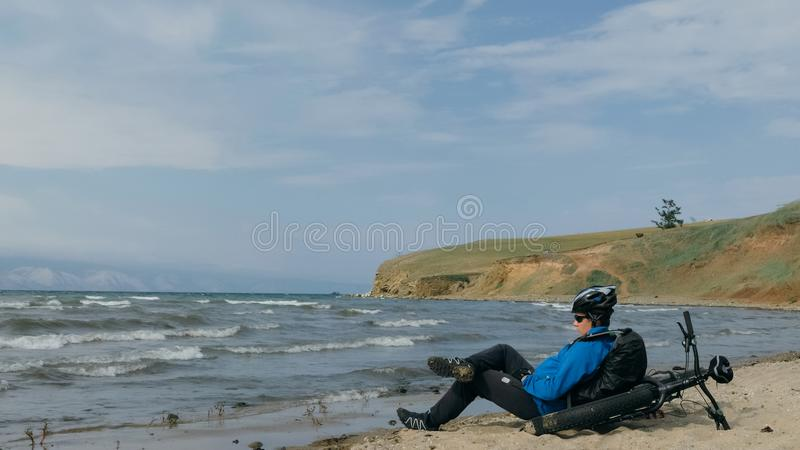 Fat bike also called fatbike or fat-tire bike in summer driving on the beach. The guy sits on the wheel of his bicycle, looks at the sea stock photography