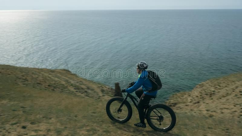 Fat bike also called fatbike or fat-tire bike in summer driving hills. Fat bike also called fatbike or fat-tire bike in summer driving through the hills. The stock image