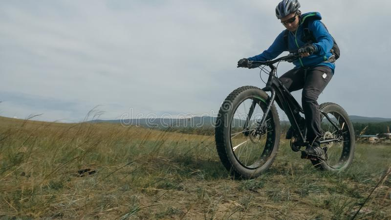 Fat bike also called fatbike or fat-tire bike in summer driving hills. Fat bike also called fatbike or fat-tire bike in summer driving through the hills. The stock images
