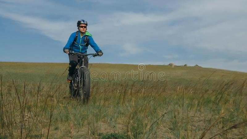 Fat bike also called fatbike or fat-tire bike in summer driving hills. Fat bike also called fatbike or fat-tire bike in summer driving through the hills. The stock photos