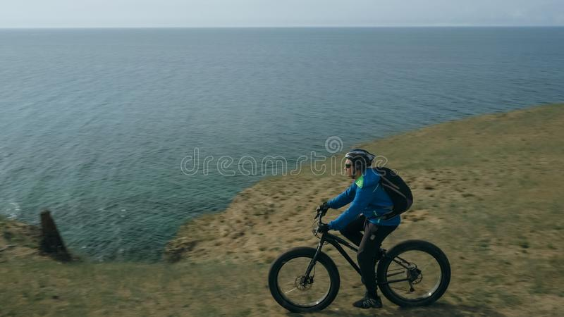 Fat bike also called fatbike or fat-tire bike in summer driving hills. Fat bike also called fatbike or fat-tire bike in summer driving through the hills. The royalty free stock photo
