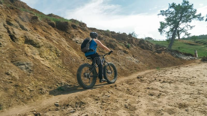 Fat bike also called fatbike or fat-tire bike in summer driving on the road. The guy rides by the hill on a sand clay path, behind him the shore by the sea stock photography