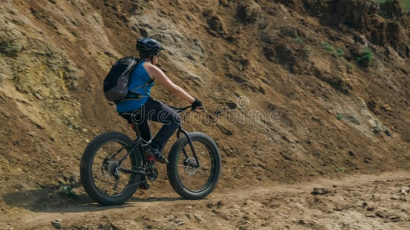 Fat bike also called fatbike or fat-tire bike in summer driving on the road. The guy rides by the hill on a sand clay path, behind him the shore by the sea stock photos