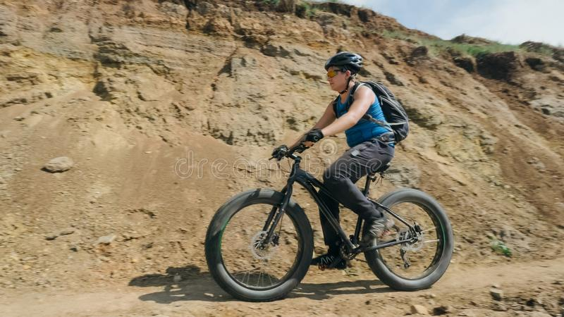 Fat bike also called fatbike or fat-tire bike in summer driving on the road. The guy rides by the hill on a sand clay path, behind him the shore by the sea royalty free stock images