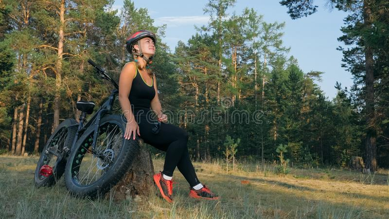 Fat bike also called fatbike or fat-tire bike in summer riding in the forest. Beautiful girl and her bicycle in the forest. She poses and smiles to the royalty free stock image
