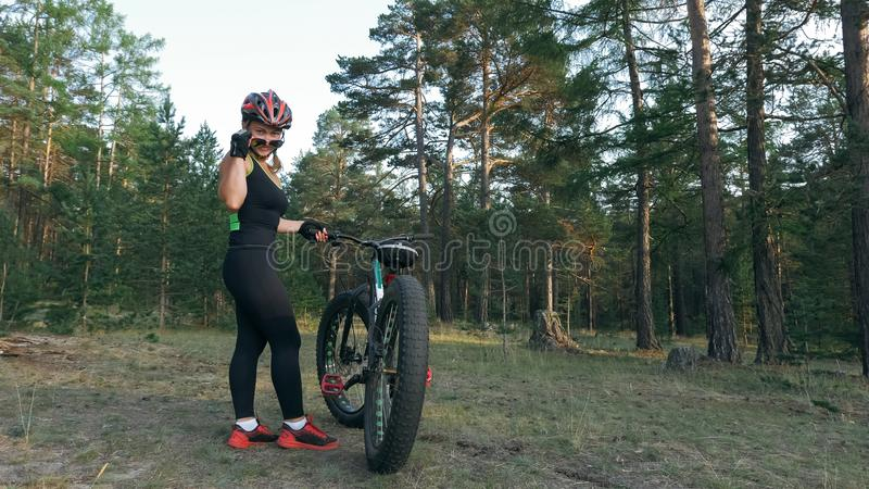 Fat bike also called fatbike or fat-tire bike in summer riding in the forest. Beautiful girl and her bicycle in the forest. She rolls her bike and poses to the royalty free stock images