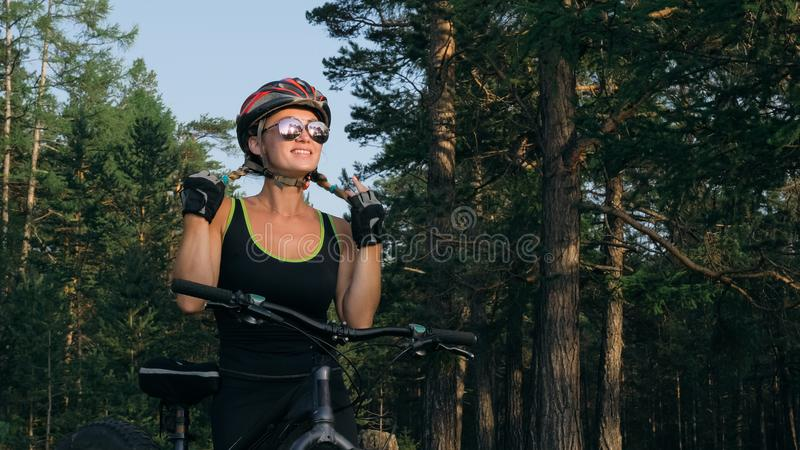 Fat bike also called fatbike or fat-tire bike in summer riding in the forest. Beautiful girl and her bicycle in the forest. She poses and smiles to the royalty free stock images