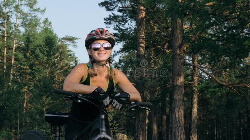 Fat bike also called fatbike or fat-tire bike in summer riding in the forest. Beautiful girl and her bicycle in the forest. She poses and smiles to the stock photography